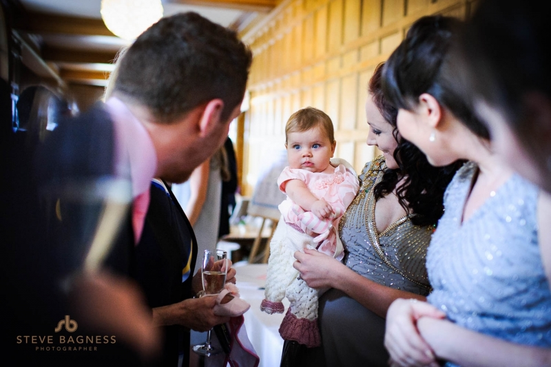 A baby girl stares out at guests during a wedding reception at Coombe Lodge
