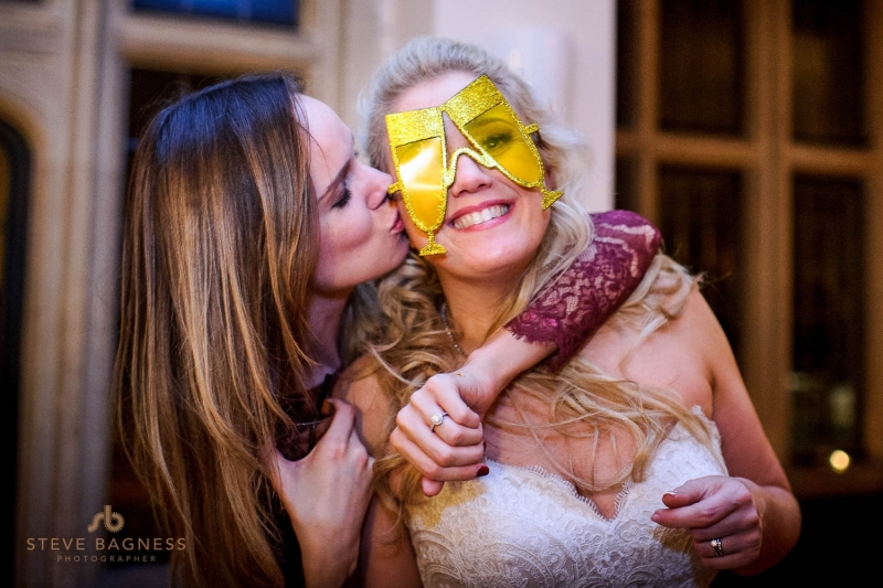 A bride and friend kiss wearing comedy glasses