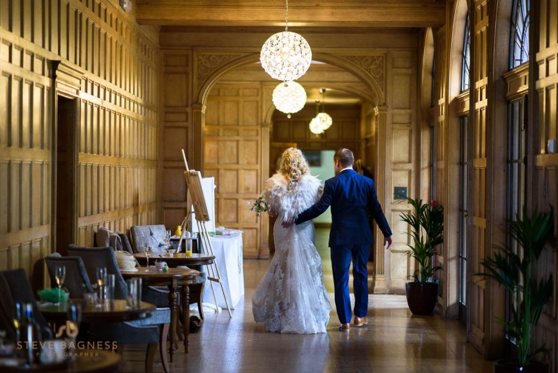 A bride and groom walk down the hallway as they leave their wedding reception