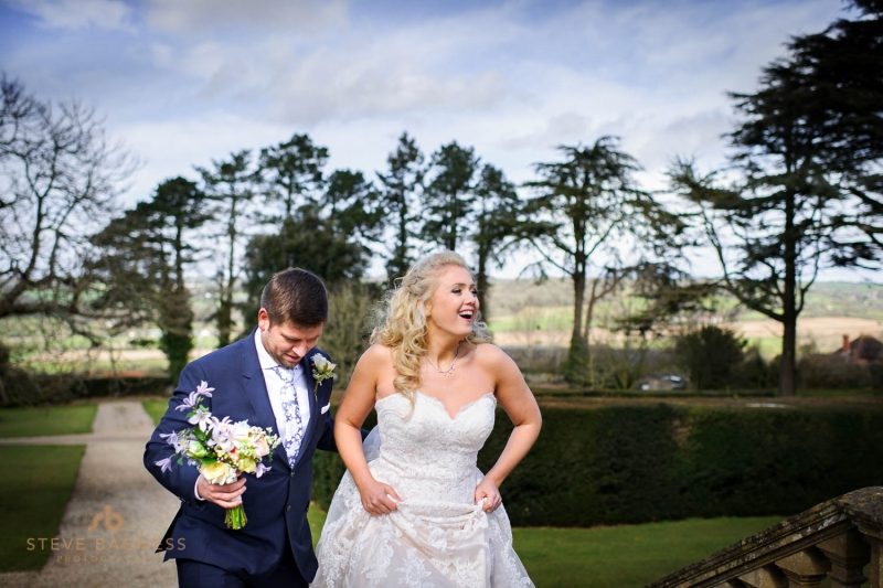 A bride and groom climb steps in the gardens of Coombe Lodge