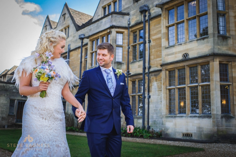 A bride and groom hold hands in front of Coombe Lodge