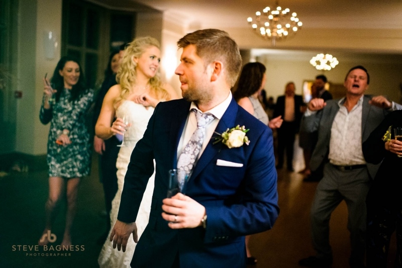 A groom dances at his wedding reception as his bride looks on