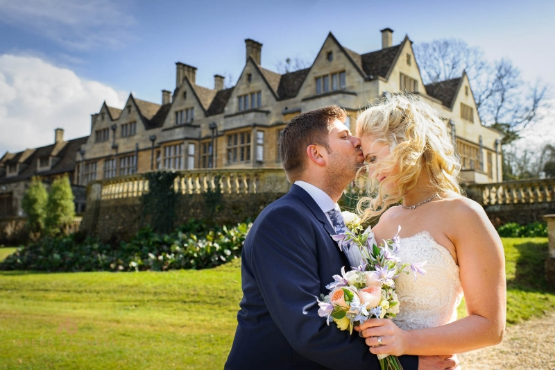 A bride and groom pose for photos in front of Coombe Lodge
