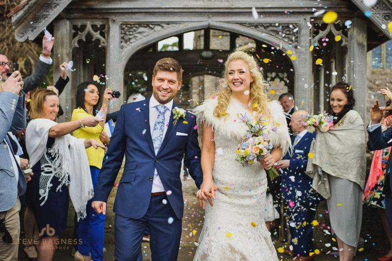 A confetti covered bride and groom leave a church in Somerset
