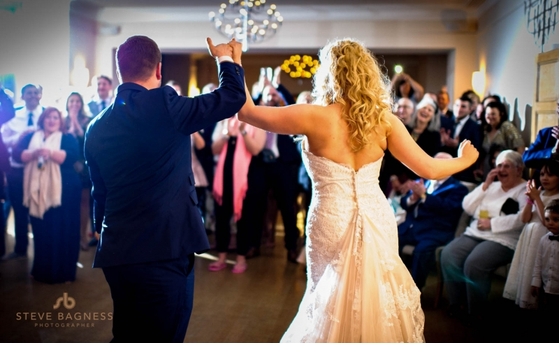 A bride and groom face the audience after their first dance