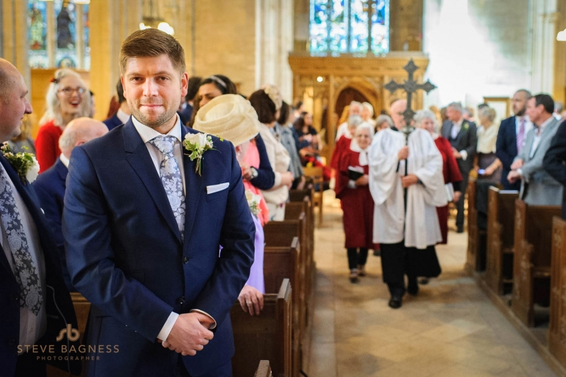 A groom smiles as his bride walks down the aisle in Somerset