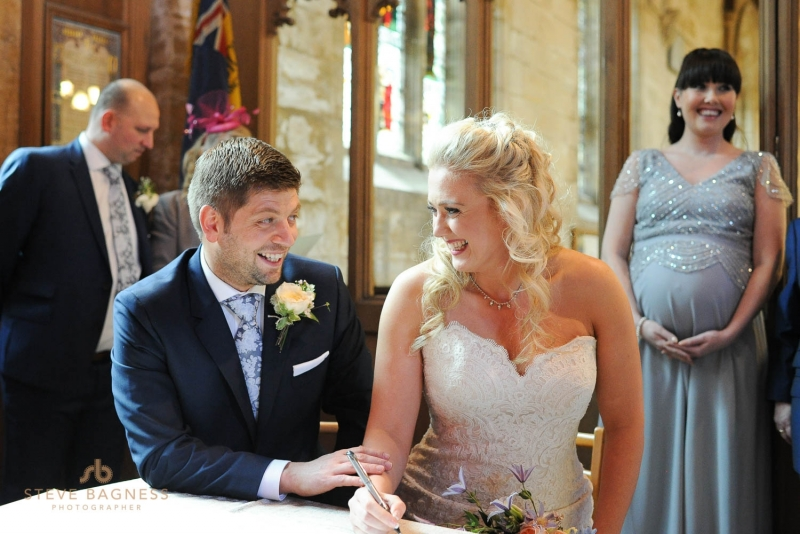 A bride and groom smile as they sign the register at Coombe Lodge
