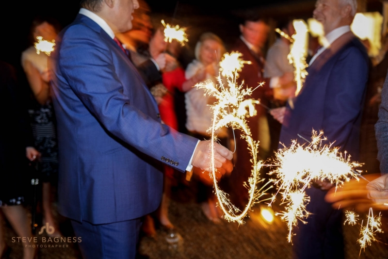 Guests light sparklers at a wedding in Wasing Park Berkshire