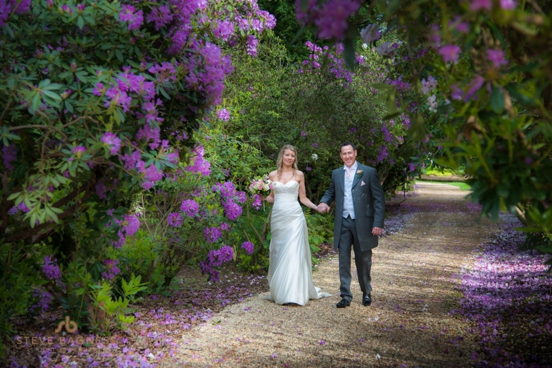 A bride and groom walk among purple flowers at a Berkshire wedding