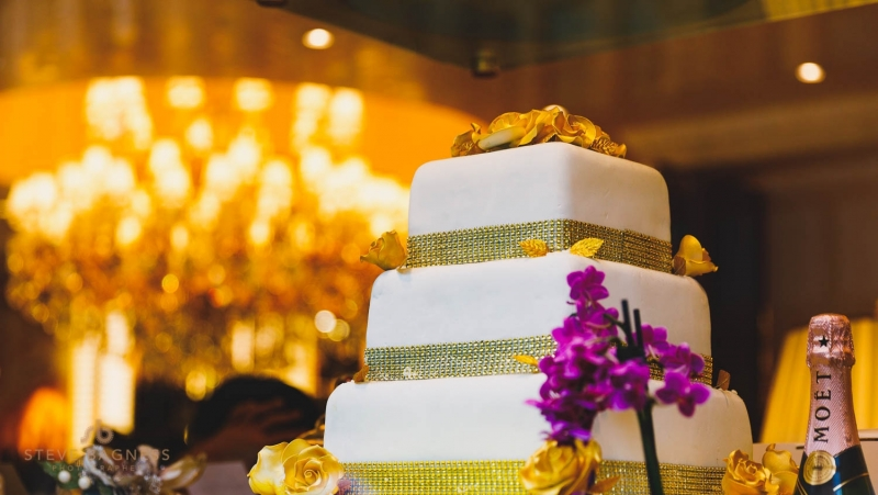 A gold and white decorated tiered wedding cake