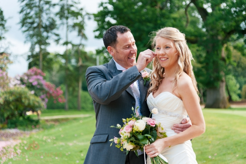 A groom removes strands of flyaway hair from his brides face